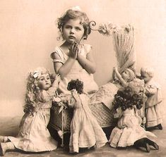 Vintage photo of little girll with her dolls saying their prayers before bed.