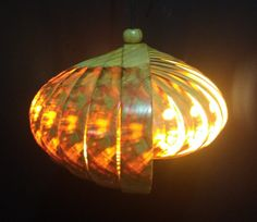 Side view of the Enigmatic oval hanging lamp (Horizontal) looks intriguing because of the shell-shape with warm white light inside.
