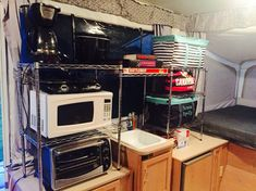 Photo by Angela Parsons. Two sets of metal racks from Walmart/Aldi/Lowe's. (14.99-24.99 each) Put them together and take apart for each trip in about 20 minutes. I store the poles under a bench seat and the shelves on the camper floor. Saves so much room and so easy!