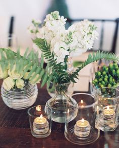 Oil tea lights add a warm glow to the small flower arrangements of white stock flowers, spray roses, and green hypericum berries at this backyard Oklahoma affair.