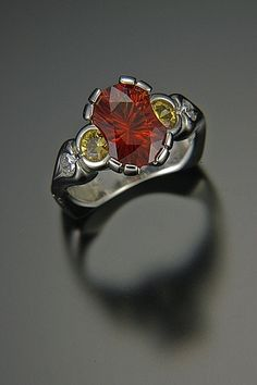 """A Palladium ring by artist Tom Dailing features a """"viola cut"""" hessonite garnet that has been concave faceted by lapidary artist Richard Homer. This center garnet is accented by round golden sapphires and pear shaped diamonds. Custom Wedding Rings, Pear Shaped Diamond, Gems And Minerals, Stone Rings, Vintage Rings, Handcrafted Jewelry, Bridal Jewelry, Jewerly, Jewelry Rings"""