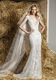 ZUHAIR MURAD Bateau Neckline Mermaid Wedding Dress A bateau neckline wedding dress in mermaid silhouette with cascading sequins on the bodice to the skirt, featuring an illusion neckline with cap sleeves.