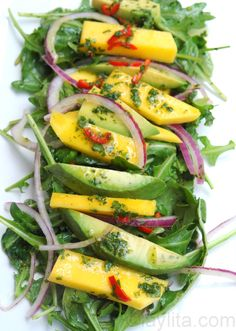 Summer arugula salad with mango, avocado and red onions tossed with spicy orange vinaigrette