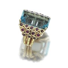 AQUAMARINE AND RUBY RING, 1940S. Claw-set with a step-cut aquamarine embellished to each side with  three rows of circular-cut rubies, to the yellow gold mount