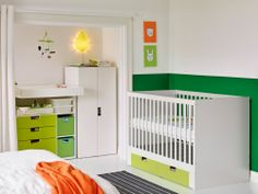 ikea.com A bedroom with a white crib with green floor drawers combined with a white wardrobe and a white changing table with green drawers.