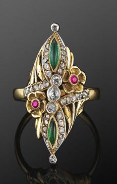 Platinum top Yellow Gold Jeweled Flower Ring, Art Nouveau.  Marquise shape emerald cabochons are set in an old mine and rose cut diamond surround with yellow gold ruby accented flower motifs in a platinum topped yellow gold mounting.