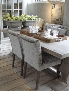 Beautiful Kitchens and Dining Rooms | Mix of velvet tufted chairs and bench seating for this pedestal dining table, wood floors with gray central accent.
