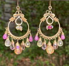 Pastel shades of genuine gemstones are wire wrapped on handmade 14kt gold filled hoop earrings to create these boho hoop chandelier earrings. The bottoms of the hoops dangle pink sapphire, lemon quartz, pink topaz and tangerine mystic topaz briolettes while the centers dangle rondelles of Ethiopian fiery opals, mystic citrine, and the bright pink, top quality pink sapphires. The gentle mystic coating on some of the gemstones give these earrings a dreamy, ethereal feeling! Coils of 14kt gold…