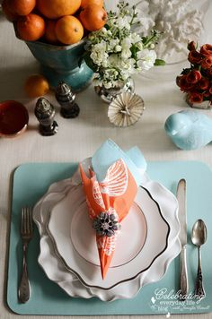 Blue Lizard Placemat from Caspari with Orange and Blue Paper napkins, DIY bejeweled napkin ring with mismatched silver flatware, ivory linen tablecloth and orange centerpiece
