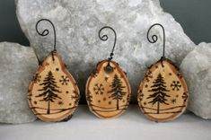 Wood burned Scandinavian Christmas ornaments. - cut sections of wood off branches/tree trunks, drill a hole at the top, and use a wood burner to draw your design.