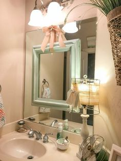Hang an empty mirror over those ugly builder grade mirrors for a fun update! How I use empty frames in my decor by CountyRoad407.com