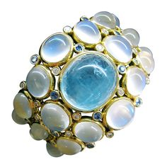 Temple St Clair Bracelet-A yellow gold very spectacular Temple Saint Clair cuff-bracelet set with a magnificent cabochon cut Aqua marine weighting about 25 carats and on both sides of it, cabochon royal blue moonstones, sapphires and diamonds. Hinged on one side.