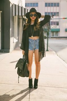 Black kimono with a black cropped top, high waisted denim short and black ankle boots accessorized with a black fedora hat, sunglasses and a detailing necklace (black bag pack)