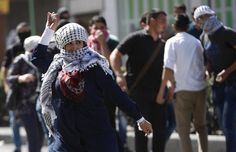 A Palestinian woman hurls stones at Israeli troops during clashes in the West Bank city of Hebron, October 13, 2015. Seven Israelis and 27 Palestinians, including nine alleged attackers and eight children, have died in almost two weeks of street attacks and security crackdowns.The violence has been stirred in part by Muslim anger over increasing Jewish visits to the al-Aqsa mosque compound in Jerusalem, Islam's holiest site outside the Arabian Peninsula. REUTERS/Mussa Qawasma