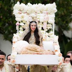 And this regal palanquin is dripping with lush pink and white peonies and garden roses.