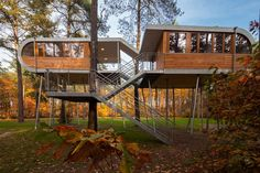 HECHTEL-EKSEL, BELGIUM - Eco-friendly tree house in the town's forests with the goal of persuading politicians and organizations to embrace sustainability. Created by German design firm Baumraum, the building is supported by 19 steel stilts and comprises two cabins—one with a technology room, pantry, and bath, the other with a meeting-and-event space.