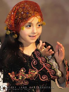 Beautiful Palestinian girl, smiles and claps.. look at her lovely clothing..