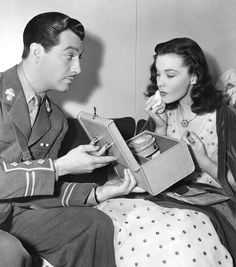 Medium BTS shot of Robert Taylor as Roy Cronin holding make-up case for Vivien Leigh as Myra Lester who is applying powder.