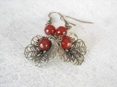 A beautiful and detailed filigree flower petal cone in brass hanging a red agate is just a perfect combination. #earrings #beads
