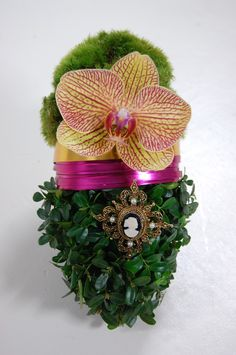 This moss and boxwood covered wet Floral Foam egg is accented by an flat wire, an orchid, and an old cameo pin.
