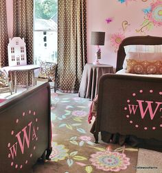 Love the colors in this room...the flowers on the walls, the rugs, and pink and brown paint on the footboards and the polkadot curtains