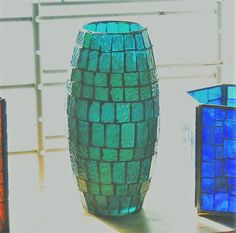 This striking Green/Blue Stained Glass Mosaic vase measures 8 tall and has a top diameter of 3 1/2. As shown in the pictures, this versatile piece can function as a vase, a decorative centerpiece, a sun catcher or as a candle holder. All thats required is a light source of some kind, and this piece can flourish beautiful ranges of green and blue depending on the intensity of the light source. If you live in a country outside of the US and want to purchase this beautiful item, pleas...