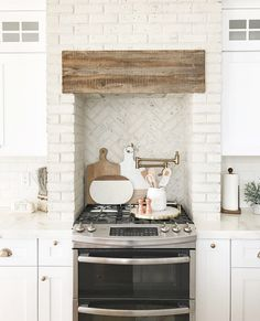 Kitchen brick hood and kitchen brick backsplash. Using distressed painted brick in kitchens is a trend that is here to stay.