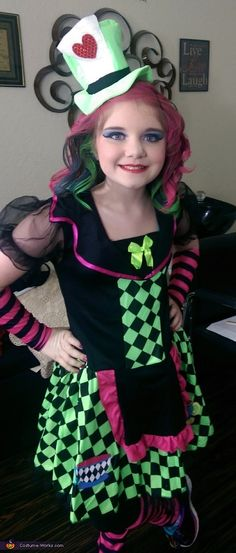 Skyla: This is Skyla and she is wearing The Lady Mad Hatter costume. Skyla chose this costume because she loves the pretty colors. We curled and airbrushed Skyla's Hair with 3...
