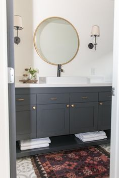 Designer Rebecca Zajac prettifies the room by replacing the cabinets with a custom vanity and laying down patterned floor tiles. Black and brass metals complement the gray and give the room a warm sophistication.