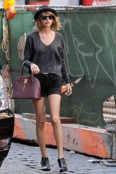 Baggy grey sweat shirt styled with black sunglasses/hat/ shorts