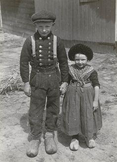Jongen en meisje in Staphorster streekdracht. Beiden zijn gekleed in de daagse dracht voor de zomer. De jongen loopt in zijn onderbroek. Zomers was het doordeweeks niet ongebruikelijk dat men hiermee in het openbaar verscheen. 1935-1945 #Overijssel #Staphorst