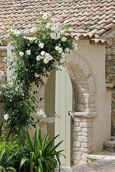 The rou estate, corfu: Stone arch covered with iceberg rose  www.clivenichols.com