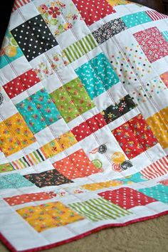 I made this bright and pretty Handmade quilt with fabrics from the Prairie collection by Moda. Scrappy patchwork squares are pieced in rows, alternating with a solid white in between, which makes the colors shine. Aqua, coral, red, yellow, green and a charcoal brown are backdrops for cute prints.