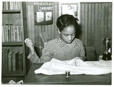Daughter of Pomp Hall sewing in school; Sewing is her 4-H club project; Creek County, Oklahoma. Alternate Title: [An African American girl sitting at desk and sewing, February 1940.]