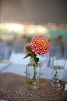 The cocktail tables will have vintage vases with single stems of coral, light pink dahlias.