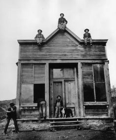 "Saloon in Wetmore (Colo.), 189,  ""Men, a boy, and a dog pose at a dilapidated saloon building in Wetmore, Custer County, Colorado. Three men sit on gabled cornices, the boy and the dog stand near the double doors, a man bends over an open window bay and another draws back a board as though to spank him."" (from the Western History/Genealogy Dept., Denver Public Library)"