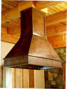 Large patinated copper range hood over kitchen island. brookscustom.com