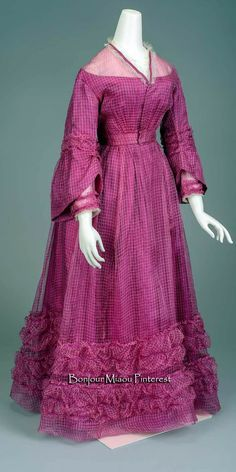 Dress, American, 1868-1870. Piña cloth; magenta with fine white line check; white tulle ruching around neck and sleeve edges. Sleeves and skirt trimmed with bands of puffed piña bound with magenta silk cloth; magenta silk lining; separate magenta silk underskirt with pocket in right front seam.