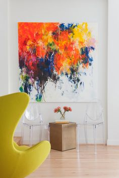 Two transparent chairs sit underneath a huge multicolor painting in this bright white modern sitting room. A small gold table is topped with a vase of flowers that bring out the colors in the painting. A modern egg chair in chartreuse is an eye catching piece in this sleek space.