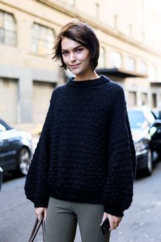 Arizona Muse in a navy cable-knit sweater + green skinny trousers