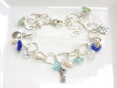This beautiful sterling silver charm bracelet is the perfect summer accessory. Sea glass in cobalt blue and sea foam green, freshwater pearls,