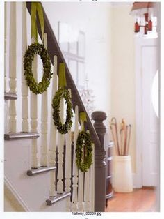 hanging wreaths on a staircase.  This would be a great family project - each person makes a wreath.