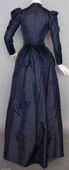 NAVY SILK DAY DRESS, c. 1888. 1-piece, soft silk twill, cross-over bodice w/ chenille yarn & navy silk ribbon tabs, princess back seams, cotton linings,19th C embroidered & fringed shaped shawl in mushroom brown silk faille. Back