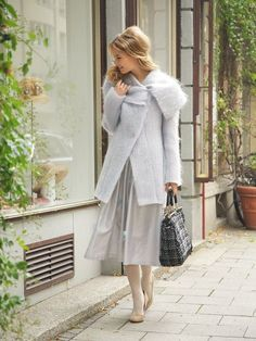 A large draped collar, fluffy fabric, concealed snap fasteners, and the flattering hip length make this coat the perfect pairing to any outfit.  $5.40
