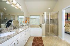 Gehan Homes Master Bathroom - Pops of orange, brushed nickel hardware, granite countertop, tan tile. Austin, Texas   Georgetown Village - Laurel #Gehanhomes