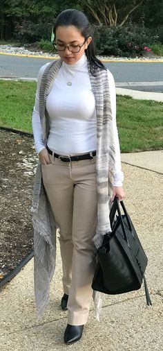Woman wearing white turtle neck paired with a beige office pants and ankle boots with a light sleeveless coat and a black Celine croc stamped phantom luggage tote - outfit idea for women in fall. More information on http://www.oneawesomemomma.com/2016/10/20/sleeveless-coat/