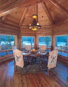 the dining area in this log home is perfect...love the round domed design surrounded by windows to keep the view unobstructed.