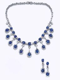 A SUITE OF SAPPHIRE AND DIAMOND JEWELRY. Comprising a necklace, designed as a fringe of graduated oval-cut sapphires and circular-cut diamonds, each suspended from a marquise-cut diamond trefoil and cushion-cut sapphire to the marquise and circular-cut diamond backchain; and a pair of ear pendants en suite, mounted in 18k white gold.