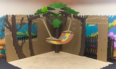 The setting is INSIDE thetree house: The walls are 8′ tall, the top of the tree is about 10′, the floor is made out of a scrap piece of linoleum. We cut the edges and painted the back side with latex house paint to look like wood flooring.