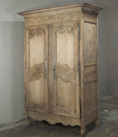 Another  work of art in antique furniture from the master artisans of Normandie, Crafted of solid French oak and hand-carved with flowers and foliage, this two-door antique Country French armoire comes from the Normandy region and was built circa 1780.